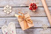 Christmas Decorations On Wooden Background. Gift Boxes With Bows, Craft Paper, Wooden Snowflakes, Kn poster