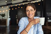 Portrait of beautiful mature woman drinking a cup of tea in cafeteria. Happy woman in a cafe drinkin poster