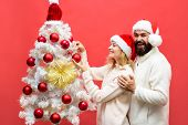 Happy Boyfriend Decorating Christmas Tree At Home With Girlfriend. Happy Family In Santa Hats Decora poster