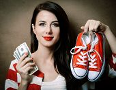 Portrait Of Beautiful Young Woman With Red Gumshoes And Money On The Brown Background poster