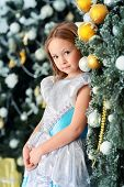 Cute six-year-old girl poses near the Christmas tree. Classic luxurious interior decorated for Chris poster