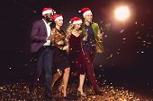 Glamorous Multiethnic Friends In Santa Hats Holding Champagne Glasses And Walking On Confetti With B poster