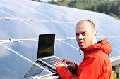 Постер, плакат: Мужской инженер используя ноутбук солнечных панелей в фоновом режиме