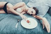 Slim Girl With Anorexia Lying On Sofa With Plate. Sliced Vegetables. Woman With Anorexia. Weigth Pro poster