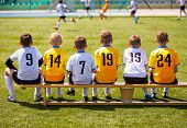 Young Football Players. Young Soccer Team Sitting On Wooden Bench. Soccer Match For Children. Young  poster