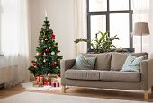 winter holidays and interior concept - christmas tree, gifts and sofa at cozy home living room poster