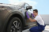 Male Worker Cleaning Automobile Door With Rag At Car Wash poster