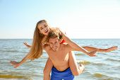 Happy Young Couple In Beachwear Having Fun Together On Seashore poster
