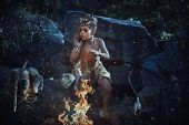 Shaman Boy At The Fire. Scary Young Primitive Boy Outdoors Near Bonfire. Witch Craft Concept. Angry  poster