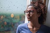 Sad African American Girl Looking Out Of The Window On Rainy Weather poster