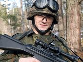 stock photo of hider  - The portrait of the soldier with rifle - JPG