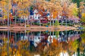 A Nice Lakeside Home With Calm Water Reflecting Autumn Trees poster