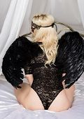 Back View Of Fallen Black Angel With Wings. Sexual Woman In Black Bodysuit And Black Wings Sitting O poster