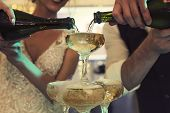 Smiling Happy Bride And Groom With Champagne Bottles Pouring Wine Into The Tower Glasses. Wedding Ch poster