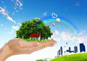 image of natural resources  - Human hand holding houses surrounded by nature against blue sky and rainbow - JPG