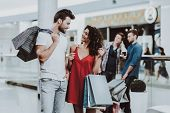 Young Couple With Packages After Shopping In Mall. Looking Into Package. Shopping Concept. Girl In R poster