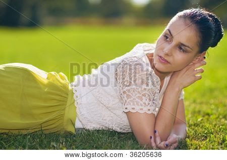 Thoughtful Young Woman Laying On Grass
