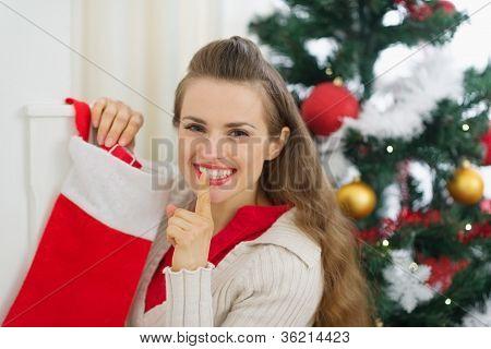 Sonriente joven ponga regalo en Navidad calcetines y mostrando Shh