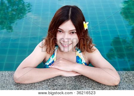 Closeup Of Beautiful Woman Resting On The Edge Of Swimming Pool