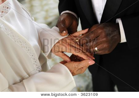 Senior Groom Slipping Ring On Bride