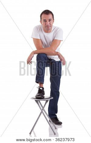Portrait Of A Handsome Middle-age Man With His Foot On A Bench, On White Background. Studio Shot