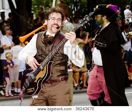 A musical performer plays for the crowd at the annual DragonCon parade