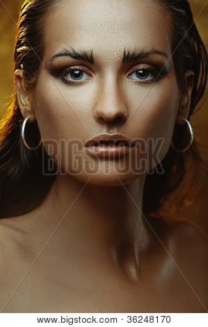 Beautiful young woman with bronze skin and gold makeup