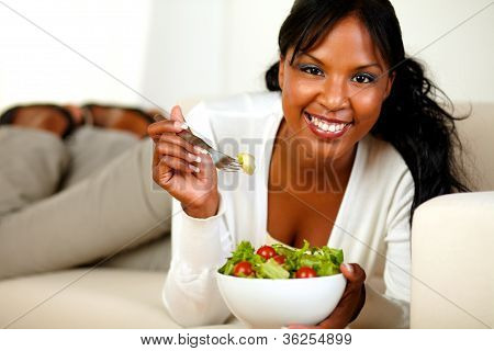 Lady Lying On A Sofa And Eating A Vegetable Salad