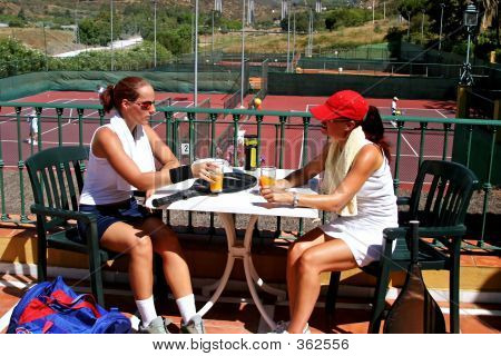 Two Women Enjoying A Cold Drink After A Game Of Tennis In The Sun