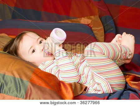 Pretty Baby Girl With Infant Formula In Bottle  On Bad. The Concept Of Childhood And Family