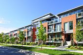foto of row houses  - Modern town houses of brick and glass on urban street taken from public location  - JPG