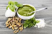 picture of pesto sauce  - Homemade pesto in bowl with spoon walnuts basil parsley and garlic on aging white ash wood background - JPG