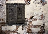 Old Weathered Wooden Shutters Covering Window In Red Brick Wall poster