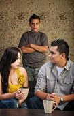pic of stubborn  - Young Latino family with stubborn son in background - JPG