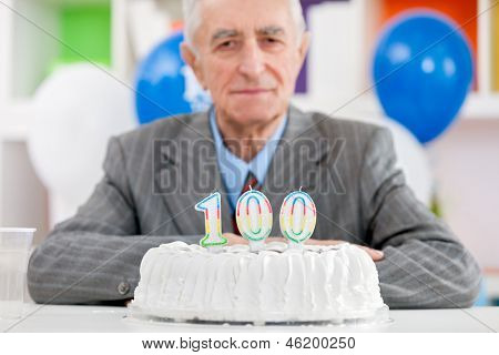 Senior man with cake on  one hundredth birthday