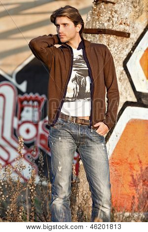 appealing guy in front of graffiti wall