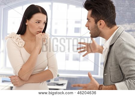 Young couple arguing, man shouting at woman.