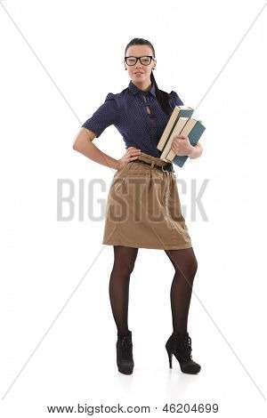 Stylish young schoolmistress posing with books in hand, other hand on hip.