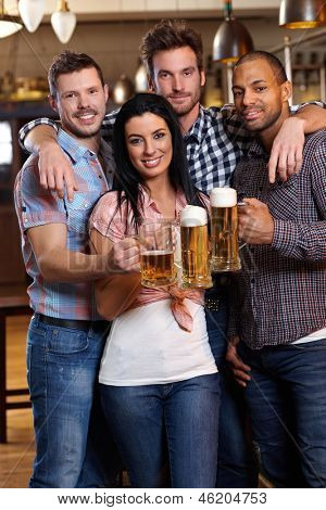 Group of happy young friends drinking beer at pub, smiling, clinking glasses