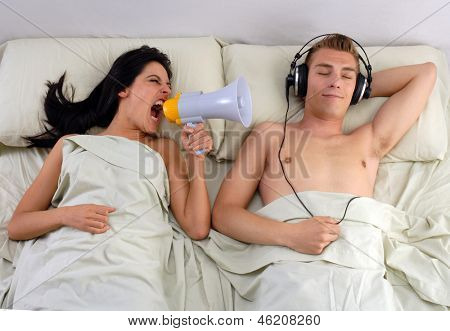 Funny couple in bed waking up in the morning.Using megaphone and headphones..