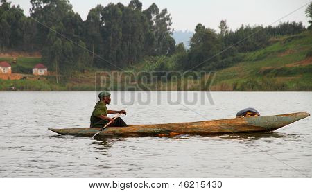 African Man Paddles Dugout Canoe