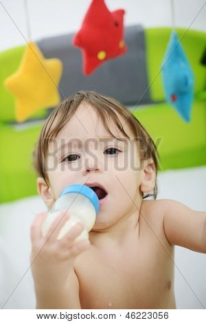 Beautiful little baby with a milk bottle in bed