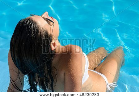 Woman relaxing and sunbathing in pool