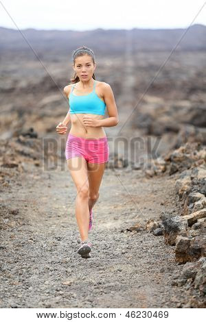 Healthy lifestyle runner woman trail running cross country running outdoors on volcano. Female athlete jogging training for marathon run outside in beautiful landscape on Big Islands, Hawaii, USA.