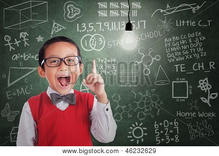 Asian Boy Has Idea Under Lit Bulb In Classroom