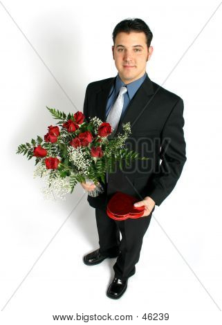 Man Holds A Dozen Roses And Candy.