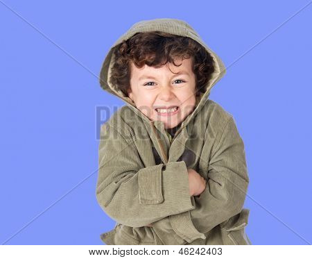 Funny little boy shivering with cold on a blue background