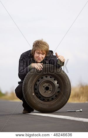 Man changing wheels being cheerful
