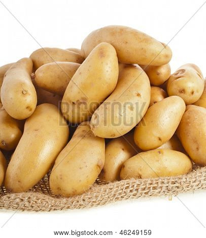 Raw potatoes heap with sack cloth close up isolated on a white background