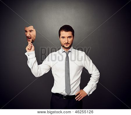 serious businessman holding mask with bad mood